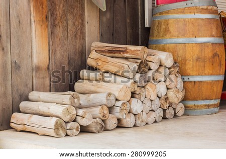 stack of firewood logs in front of a hut. - stock photo