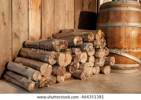 Stack of firewood stick and wooden barrel.