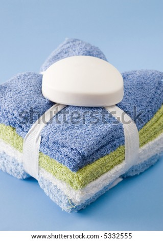 Stack of folded washcloths isolated on blue with bar of soap on top. - stock photo