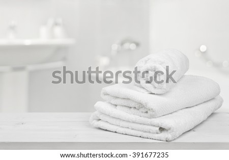 Stack of folded white towels over blurred bathroom background - stock photo