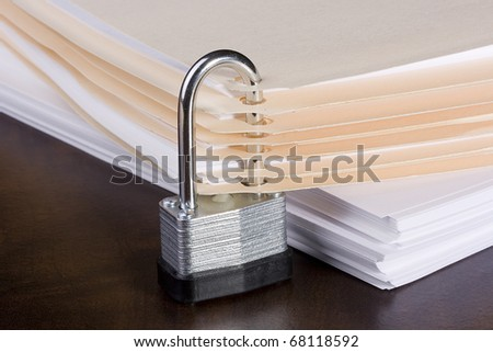 Stack of folders closed with a metal lock. - stock photo
