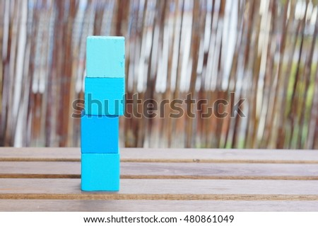 Stack of four blue square wooden toy blocks on table