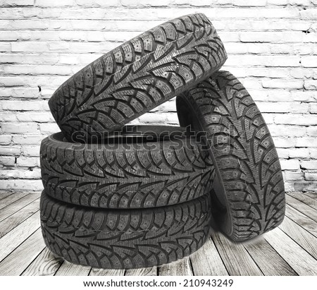 Stack of four new black tyres for winter car on  wooden floor in vintage room with brick wall background - stock photo
