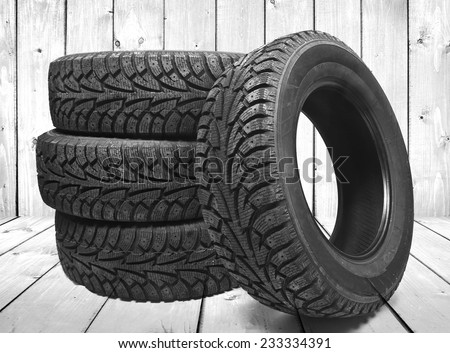 Stack of four new black tyres for winter car on wooden floor in vintage room with wall background  - stock photo