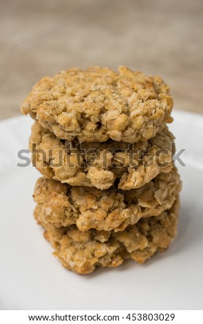 Stack of four oatmeal cookies on white plate - stock photo