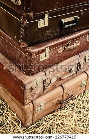 Stack of four vintage suitcases on hay - stock photo
