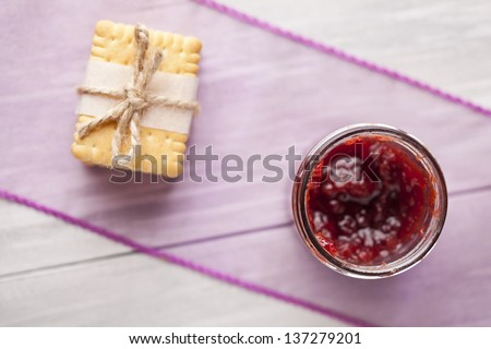 Stack of fresh baked biscuits tied with vintage string and jar of red fruit jam. Sweets composition taken on white table. - stock photo