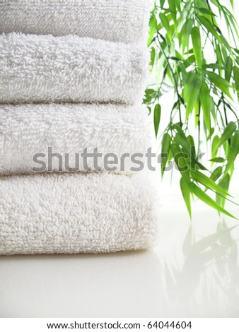 Stack of fresh white towels with blurred bamboo background - stock photo