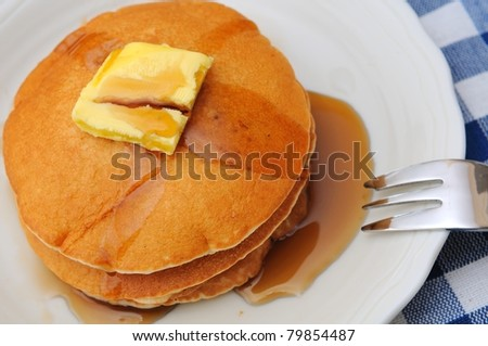 Stack of freshly made delicious pancakes topped with butter and sweet maple sauce. - stock photo