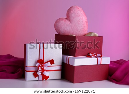 Stack of gift boxes and decorative heart, on color background - stock photo