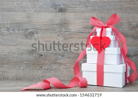 Stack of gift boxes with ribbon and bow  on old wooden background - stock photo
