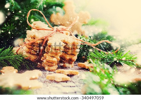 Stack of Ginger Cookies Snowflakes tied up by a Rope in Christmas Composition Decorated with Fir Tree. Illustrated with Drawn Snow. Warm Toned  - stock photo