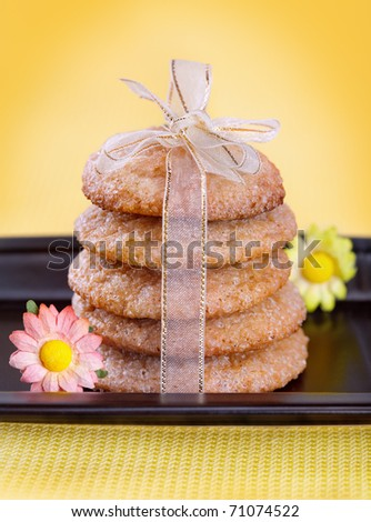 Stack of gingerbread cookies tied with ribbon on black plate - stock photo