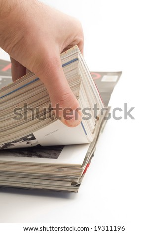 Stack of glossy magazines,hand browsing pages - stock photo