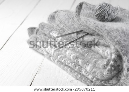 Stack of gray warm fluffy knitwear with knit needles and ball on white wood. Shallow DOF. - stock photo