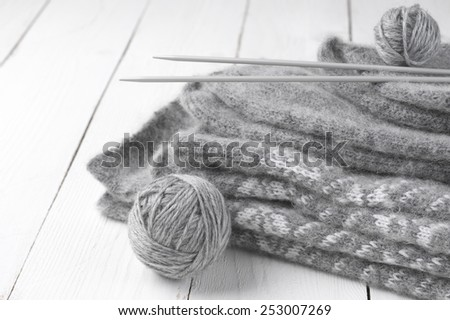 Stack of gray warm fluffy knitwear with knit needles and balls on white wood. - stock photo