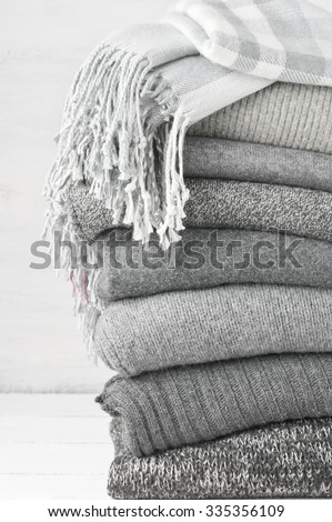 Stack of gray woolen knitted sweaters and shawl with fringe. - stock photo
