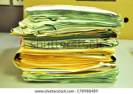Stack Of Green And Yellow Folders On The Table - stock photo
