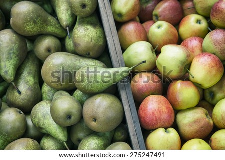 Stack of green pears next to pile of fresh red and green apples on display in outdoor baskets at farmers fruit market  - stock photo