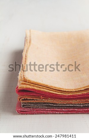 Stack of hand made colorful placemats napkins on white background - stock photo