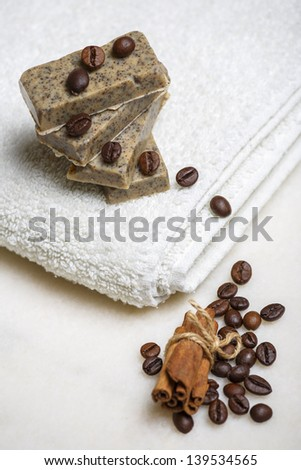 Stack of handmade flavored soap bars surrounded by coffee beans and cinnamon on white towel. - stock photo