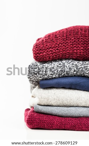Stack of handmade wool sweaters isolated