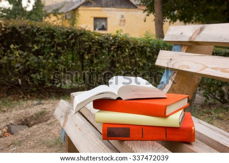 Stack of hardback book and Open book lying at park on blurred nature backdrop. Copy space for text, back to school. Education background. - stock photo