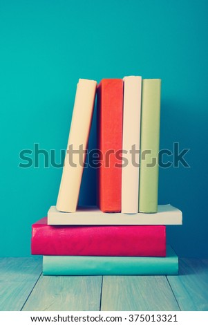 Stack of hardback books on blue wooden shelf table background. Instagram vintage toned photo. Books stacking. Back to school. Copy Space. Education background. - stock photo