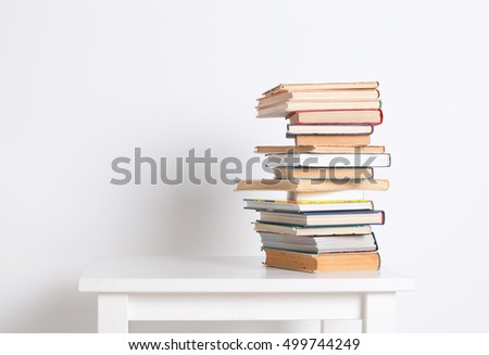 Stack of hardback books on the white table on white wall background.  Search for relevant and necessary information in a large number of sources during studies or work.