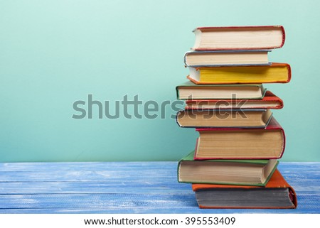 Stack of hardback books on wooden table. Back to school. Copy space for text - stock photo