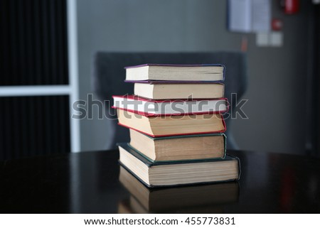 stack of hardcover books on wooden table in library. - stock photo