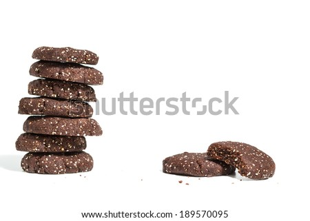 Stack of healthy dark chocolate cookies with raw cacao and chia seeds on white background - stock photo