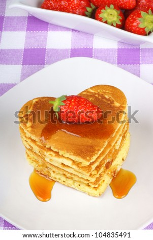Stack of heart-shaped pancakes with syrup and a strawberry on a white dish with fork. A perfect breakfast for Valentine's Day.