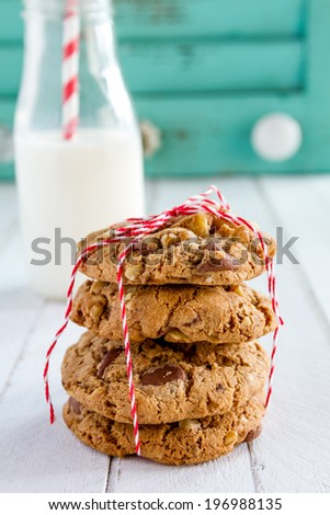 Stack of homemade chocolate chip cookies tied with red bakers twine and glass of milk with red striped straw - stock photo