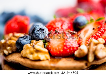 Stack of Homemade Chocolate Pancakes for Breakfast with Strawberries, Blueberries, Walnuts and Chocolate. Selective focus, shallow DOF - stock photo