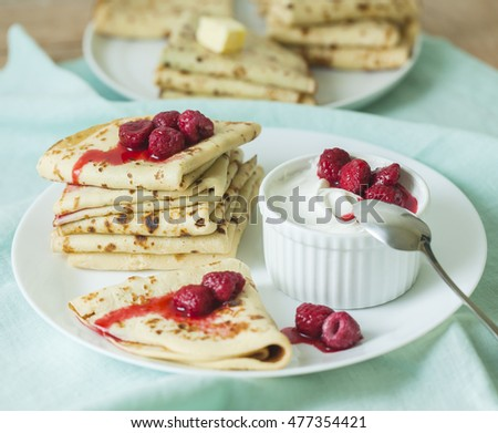 Stack of homemade pancakes with raspberry and sour cream