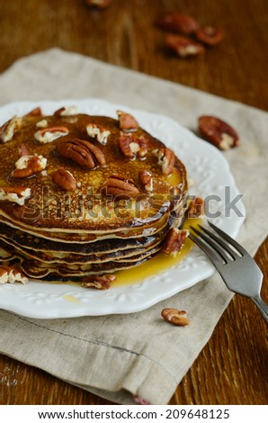 Stack of homemade thin pancakes topped with honey and pecan nuts on brown wooden table - stock photo