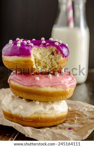 Stack of homemade vanilla bean donuts with colorful icing sitting on wooden table with glass of milk with pink striped straw - stock photo