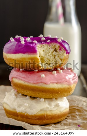 Stack of homemade vanilla bean donuts with colorful icing sitting on wooden table with glass of milk - stock photo
