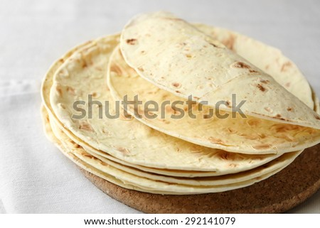 Stack of homemade whole wheat flour tortilla on napkin, on light background - stock photo