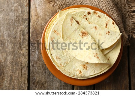 Stack of homemade whole wheat flour tortilla on plate, on wooden table background - stock photo