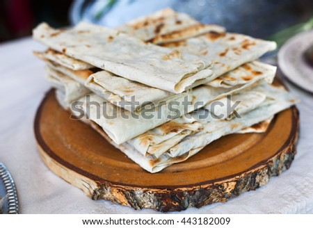 Stack of homemade whole wheat flour tortillas on a wood. Pitas for sale at picnic outdoors, closeup. - stock photo