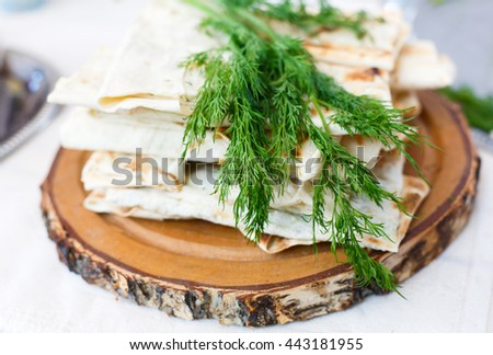 Stack of homemade whole wheat flour tortillas with fresh dill on wooden round desk. Pitas for sale with fennel at picnic outdoors, closeup. - stock photo