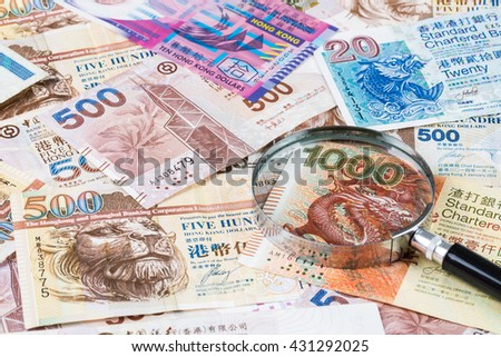 Stack of Hong Kong Dollar or banknotes with magnifying glass