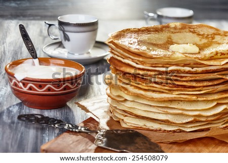 stack of hot pancakes with butter on the board and a bowl of sour cream - stock photo