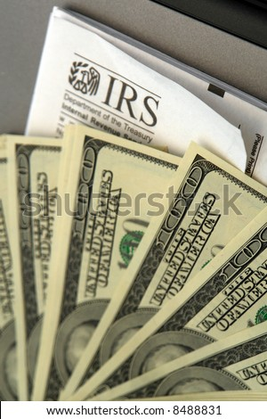 Stack of hundred dollar bills laid out on top of IRS form, paying taxes or getting a refund