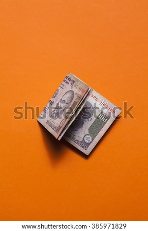 Stack of indian currency on an orange background.