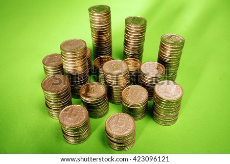 Stack of Indian rupee coins on green background