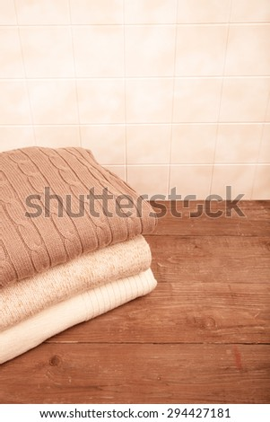 Stack of knitted clothes on wooden table opposite a tile wall. Toned.