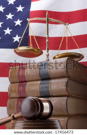 Stack of law books with gavel, scales of justice, and flag in background - stock photo